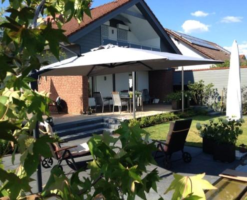 Ein kleiner Hausgarten mit Terrasse aus Naturstein