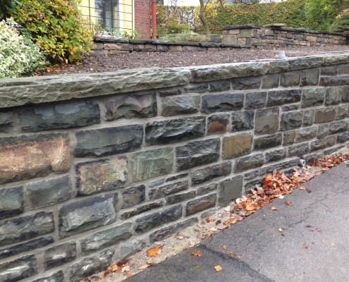 Eine Grauwackemauer mit Abdeckplatten aus historischem Material