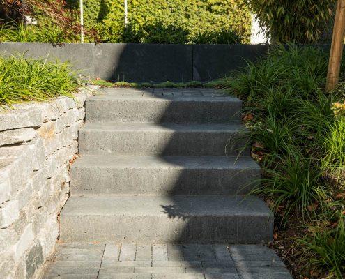 Treppe und Natursteinwand im Vorgarten